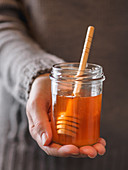 Hand holding small jar of fresh honey with spoon