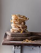 Getrocknete Pappardelle auf Holzbrett