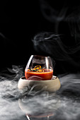 Composition of glass in bowl filled with red spicy alcohol cocktail and served on table in smoke against black background