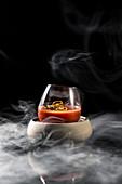 Bloody Mary mit Chili im Glas, umgeben von Rauch