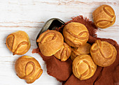 Baked round buns laid on brown napkin on wooden background