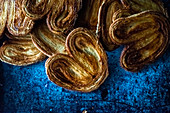 Palmier cookies laid in pile on blue background