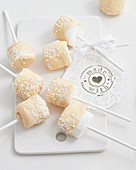 Marshmallows on sticks with white chocolate and sugar sprinkles