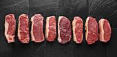 Several raw steaks on a black slate plate