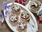 Vegan blackberry and chocolate tartlets with almond flakes