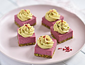 Raw vegan raspberry and pistachio cubes topped with lemon cream