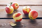 Äpfel auf Holzuntergrund, einer teilweise geschält