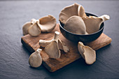 Frische Austernpilze im Schälchen und auf Holzbrett