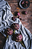 Large and small violet artichokes on a cloth and a wooden surface