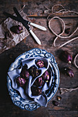 Small violet artichokes in a ceramic bowl on a wooden surface
