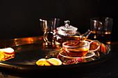 Glasteekanne und Teetasse auf Metalltablett