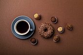 Chocolate donuts with truffles and cup of black coffee