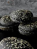 Black burger rolls with sesame seeds
