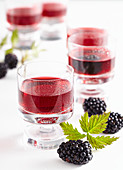Glasses of homemade blackberry and vanilla liqueur with fresh berries
