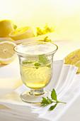 A glass of homemade limoncello with fresh lemons on a napkin