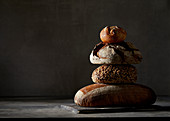 Three different breads and a bread roll, stacked