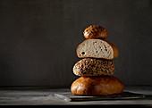 Drei Brote und ein Brötchen, gestapelt vor dunklem Hintergrund