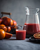 Blood orange juice in a glass jug with fresh fruit