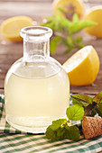 Homemade lemon syrup with mint and lemon balm in a vial