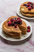 Stacked pancakes with berries and jam