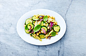 Penne pasta with courgette, red onion and chickpeas