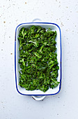 Raw kale with olive oil and spices for kale chips