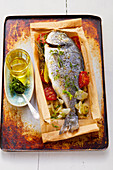 Herb dorade in paper with tomatoes and fennel