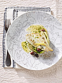 Plaice fillet with a lemon and caper sauce on a chicory and olive medley