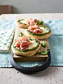 Mini pizzas with spinach and pistachio pesto, cheese and ham