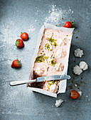 Strawberry parfait with pistachio nuts and meringue dots