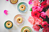 Mini vanilla Bundt cakes on a table next to a bouquet of roses