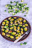 Baked Brussels sprouts on a plate and fresh Brussels sprouts