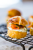 Savoury Hot Cross Bun burger with salmon and cream cheese