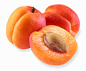 Two apricots and half an apricot on a white surface
