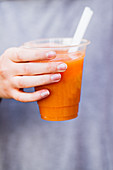 A hand holding a cup of fresh-pressed fruit juice