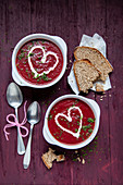 Beetroot soup garnished with yoghurt hearts and dill