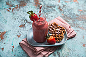A strawberry smoothie served with biscuit baked in a waffle iron (vegan)