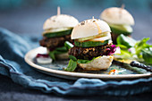 Vegan mini burgers with beluga lentil fritters, lamb's lettuce, radicchio, cucumber, onions and chilli sauce