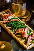 A tart with green asparagus, peas and bacon for an Easter high tea