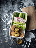 Falafel, a dip on lettuce leaves, radishes and cucumber in a lunchbox