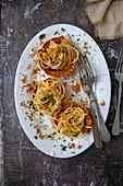 Spaghetti with pumpkin cream served in pumpkin tartlets