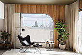 Klassikerstuhl mit Fußhocker vor Fenster
