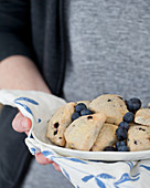 A woman holding a platter of blueberry scones with fresh blueberries