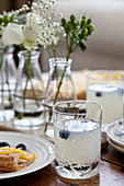 A brunch table with lemonade with blueberries, lemon tart and flowers