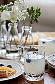 Limonade mit Blaubeeren und Blumen auf Tisch