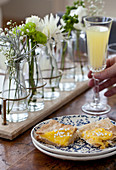 A brunch table with a lemon tart, flowers and champagne with orange juice