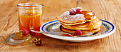 Pancakes with homemade apricot syrup and raspberries