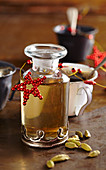 Homemade cardamom syrup in a glass carafe for Christmas