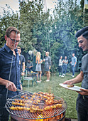 Men grilling turkey skewers on a hanging grill at a garden party