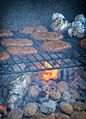 Spicy burger paties on a grill rack above glowing coals